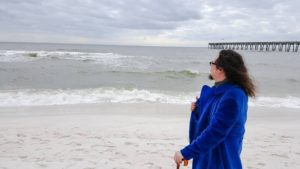 A portrait of a violent communist wearing a blue crushed velvet coat and holding an amber-handled cane, as he gazes out at the waves on Pensacola Beach, Florida on January 25, 2015.